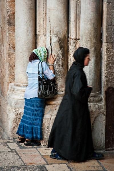 Prawosławna zakonnica i kobieta całująca popękaną kolumnę